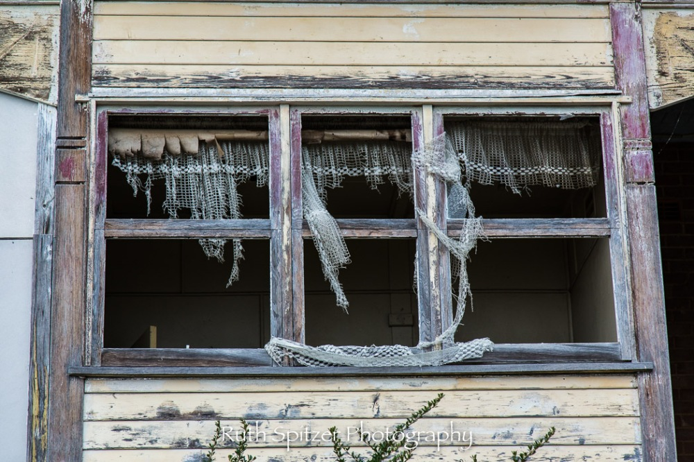 Curtain flying through a broken window at the Abandoned St Johns Orphanage in Goulburn. Image by Ruth Spitzer